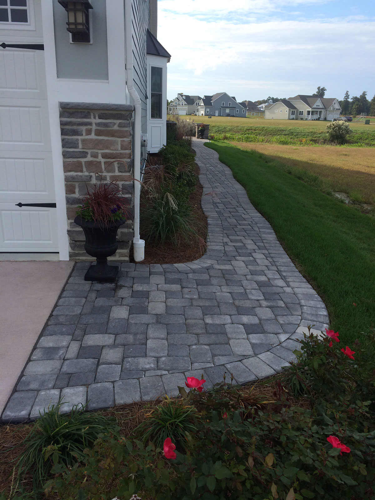 finished stone pathway on side of house with garden