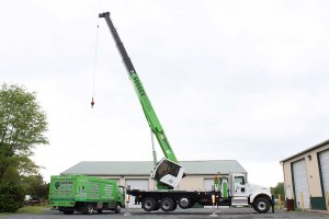 Crane in use hovering over large green truck